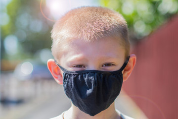 Portrait of a boy wearing her protective facial mask correctly outdoor. Concept of coronavirus.