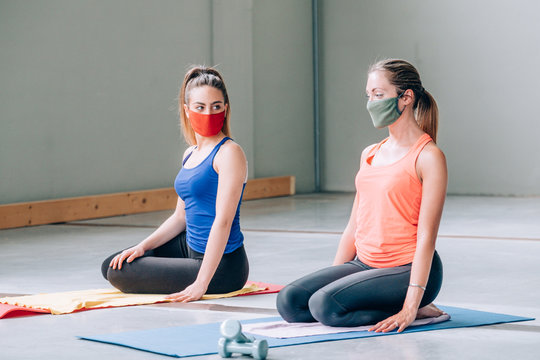 Two beautiful girls doing yoga for relax with protective masks in a gym with sports clothes - Quiet meditation in the face of a virus epidemic - Training during quarantine in the gym