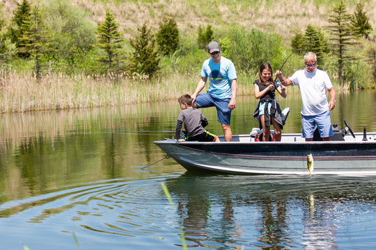 Teenage girl on a boat reeling in a bass fish with her grandpa and dad