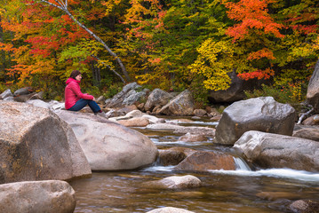 Lonely woman sitting on a rock on a forest river on a fall day. Stunning autumn colours in background.