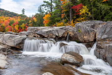 Beautiful waterfall along a mountain river on a cloudy autumn day. Stunning autumn colours in background. White Mountains, NH, USA.