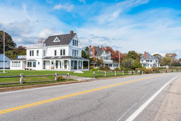 Deserted stretch of a coast road lined with beautiful detached houses on a clear autumn day. New England, USA.