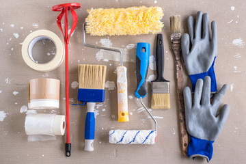 Painting tools for home decoration lying on a stained cardboard