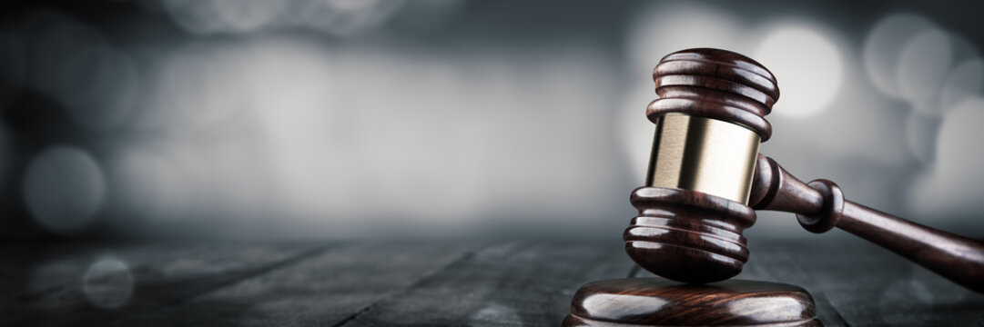 Gavel And Block On Wooden Desk With Bokeh Background - Law And Justice / Auction Concept