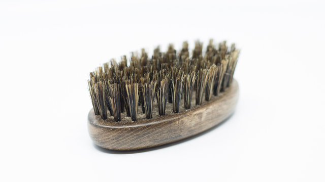 beard care brush. wooden oval brush with rough bristles isolated on white background