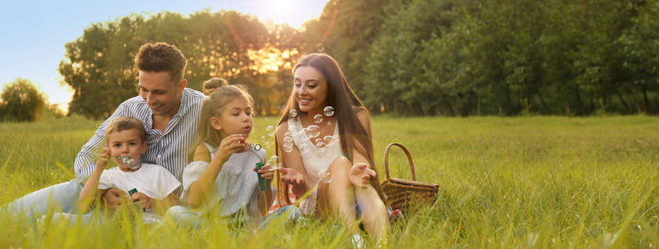 Happy family having picnic and blowing soap bubbles in park at sunset, space for text. Banner design