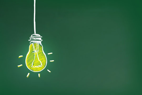 Light bulb drawing as symbol of idea on green chalkboard