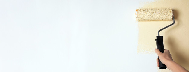 Professional decorator painting white wall with beige dye, space for text. Banner design