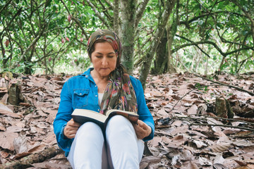 Middle-aged woman reading a book in the middle of the forest.