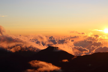 Poster Volcano An incredible sunrise as the sun crests over the cloud covered Haleakala Crater in Haleakala National Park in Maui, Hawaii