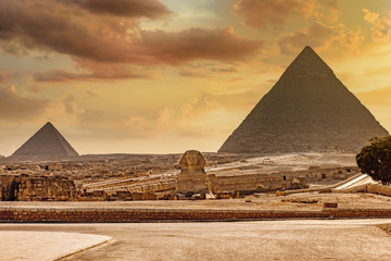 Carved great Sphinx in front of Pyramid of Giza in Egypt with dramatic yellow sky. Fotomurales