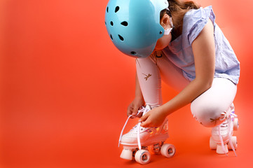 Little child with roller skates, a blue helmet on a red background, tying shoelaces. A girl of 7 years old poses and prepares for active leisure on retro ice skates. Copy space