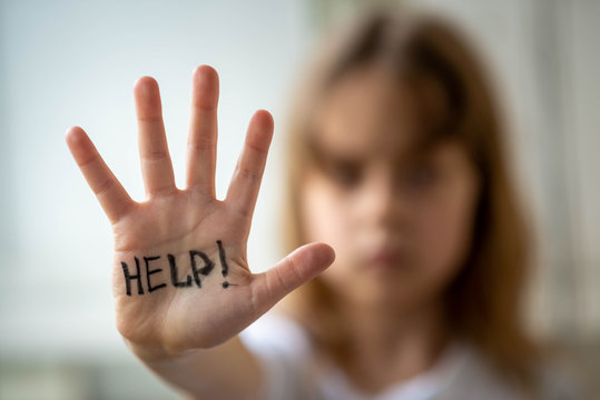 Little girl asks for help, help written on hand. Domestic and child abuse.