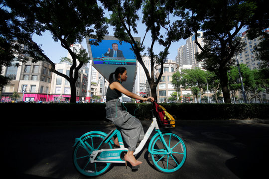 Woman cycles past a screen showing a news conference by Chinese Premier Li Keqiang in Beijing