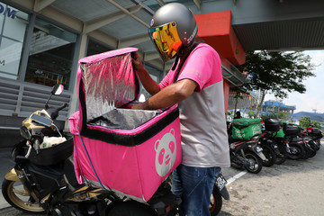 A Foodpanda rider gets ready for a delivery outside a shopping mall, amid the coronavirus disease (COVID-19) outbreak in Kuala Lumpur