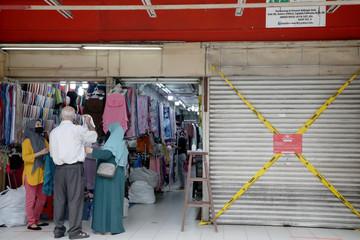 Shoppers shop next to a closed store, amid the coronavirus disease (COVID-19) outbreak in Kuala Lumpur