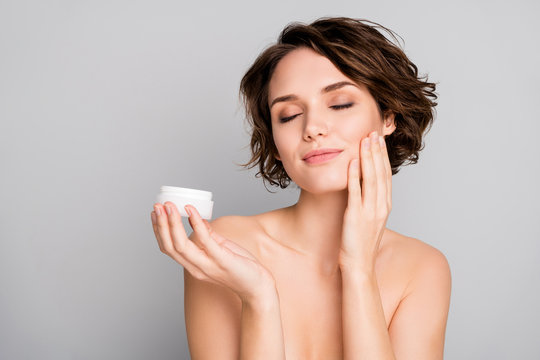 Closeup photo of beautiful attractive lady short bob hairdo hold new daily night treatment cream jar apply cheekbone eyes closed pleasant effect isolated grey color background