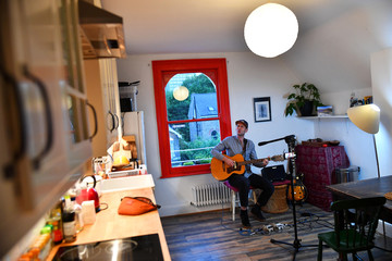 Musician Theo Bard sings as he performs an online gig from his kitchen in London