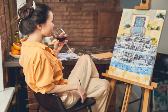 Charming lady drinking wine and looking at painting