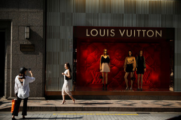 A woman poses for photographs in front of a luxury shop amid social distancing measures to avoid the spread of the coronavirus disease (COVID-19), in Seoul
