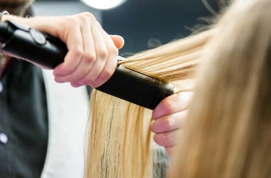 Professional hairdresser straightening long blond hair using straightener