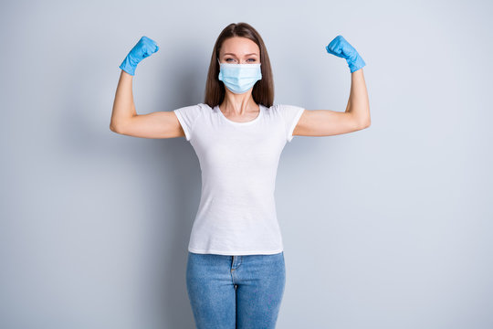 Photo of cool lady raise fists demonstrate strong immune system virus immunity self-confident person sport save world wear latex gloves protect face mask isolated grey color background