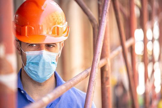 Ingegnere con casco arancio e camicia blu indossa una mascherina protettiva dentro un cantiere con delle impalcature in ferro