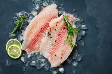 Fresh fish fillet of sea bass in ice on a dark slate background. Top view.