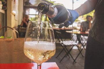 Bar tender pouring sparkling wine on a glass wearing safety gloves. Coronavirus phase 2 concept Reopening of the restaurants, bar and food and drink activities.