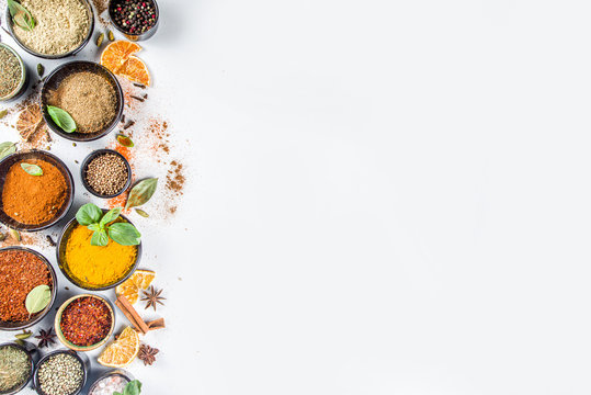 Set of Spices and herbs for cooking. Small bowls with colorful  seasonings and spices - basil, pepper, saffron, salt, paprika, turmeric. On white stone table background top view copy space
