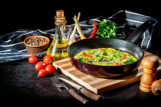 Tasty frittata with spinach and herbs in an iron frying pan on an dark background. Fritatta with broccoli