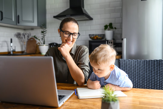 Business mom works from home. Young woman working on a distance with laptop in the kitchen, a little son is near.