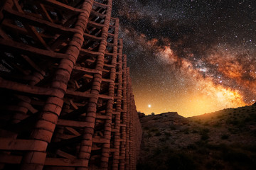 Garden Poster Brown Beautiful night landscape with bright milky way and old stone building.
