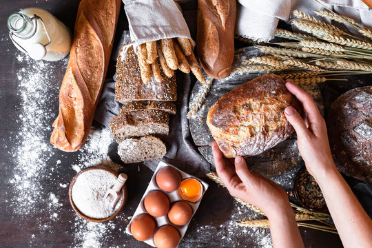 Concept of homemade bread, natural farm products, domestic production. Healthy and tasty organic food. Woman baked round whole grain bread. Top view flat lay, dark black background.