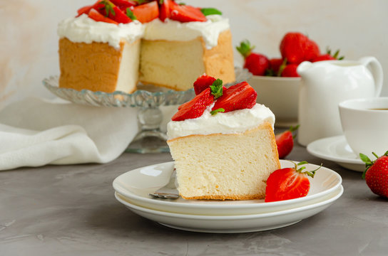 Angel food cake with whipped cream and slices of fresh strawberries on top on a concrete background. Summer dessert. Horizontal orientation, copy space.