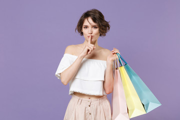 Secret woman in summer clothes hold package bag with purchases isolated on violet background. Shopping discount sale concept. Mock up copy space. Saying hush be quiet with finger on lips shhh gesture.
