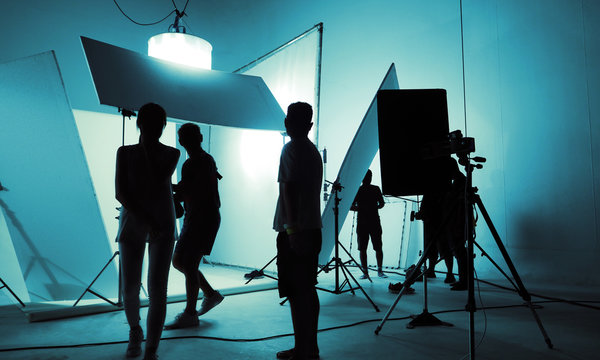 Shooting studio for photographer and creative art director with production crew team setting up lighting flash and LED headlight on tripod and professional equipment for portrait model photo shoot