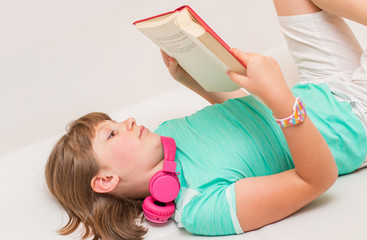 young girl child is reading book on the sofa at home