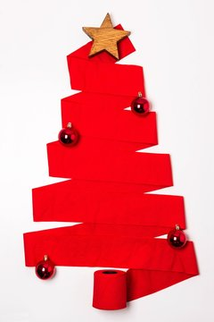 Vertical shot of a red Christmas tree made from a toilet paper roll with ornaments under the lights
