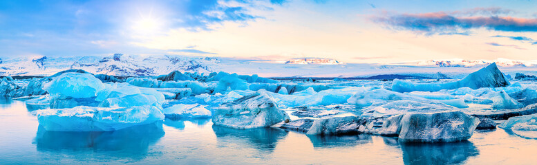 Icebergs float on Jokulsarlon glacier lagoon, with background mountain peaks lit by sunrise, in Iceland.