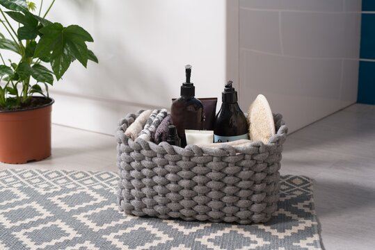 Closeup of toiletries in a yarn basket on the floor