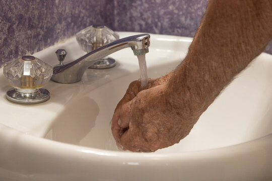 Bathroom sink cupping hands under running water