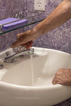Bathroom sink man's hand turning on water
