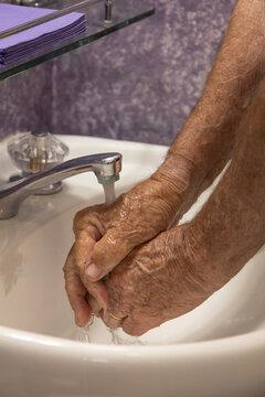 Hands under running water faucet