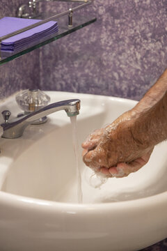 Man soaping hands in bathroom sink with running water from faucet