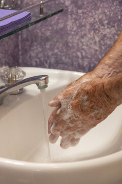 Soaping hands with running water bathroom sink vertical