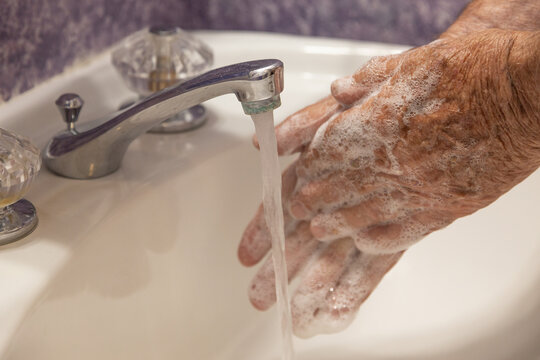 man washing hands in bathroom with soap