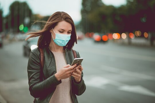 Young woman using smart phone in the city wearing face mask protection for virus coronavirus covid 19