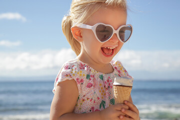 Adorable toddler girl eating ice cream. Portrait of child wearing sunglasses and holding an ice cream with beautiful blue sea and sky behind. Happy summer vacation on the beach.
