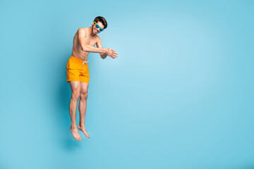 Full length body size view of his he nice attractive cheerful sportive guy in swimming shorts jumping pretending diving isolated on bright vivid shine vibrant green blue turquoise color background